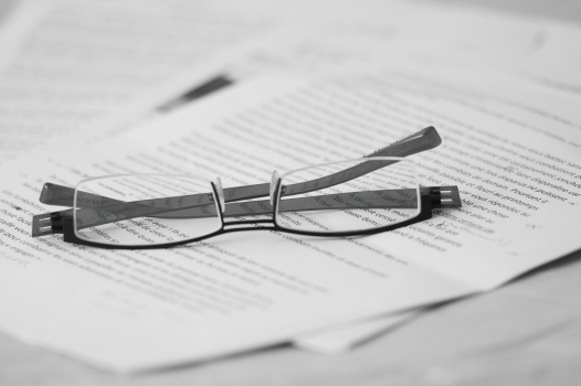 glasses sitting on a pile of papers